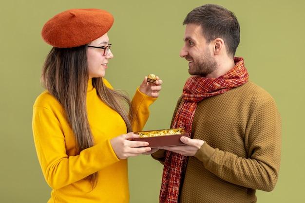 緑の壁の上に立っているバレンタインデーを祝うベレー帽で彼の笑顔の素敵なガールフレンドにチョコレート菓子を提供する若い美しいカップル幸せな男