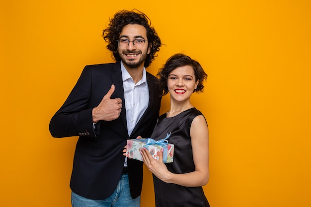 Young beautiful couple happy man showing thumbs up and woman with present looking at camera smiling cheerfully celebrating international women's day march 8 standing over orange background