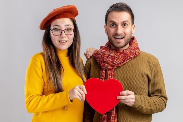 Giovane bella coppia uomo felice e donna sorridente in berretto tenendo il cuore di cartone felice innamorato insieme per celebrare il giorno di san valentino in piedi sul muro bianco