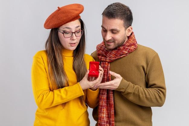 Giovane bella coppia uomo felice e donna sorridente in berretto con anello di fidanzamento nel riquadro rosso che celebra il giorno di san valentino in piedi su sfondo bianco