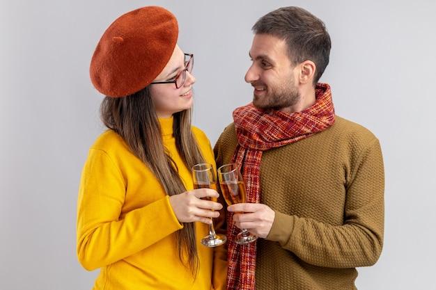 Giovane bella coppia uomo felice e donna sorridente in berretto con bicchieri di champagne sorridendo allegramente felice innamorato insieme celebrando il giorno di san valentino in piedi sul muro bianco