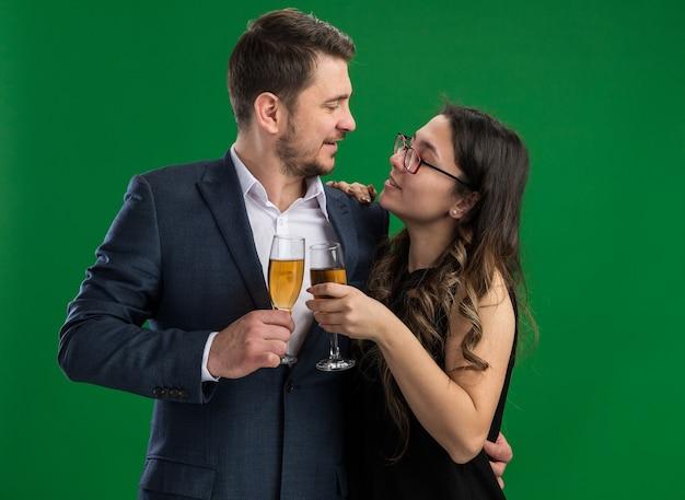 Giovane bella coppia uomo felice e donna sorridente con bicchieri di champagne che si abbracciano guardandosi felici innamorati insieme celebrando il giorno di san valentino in piedi sul muro verde