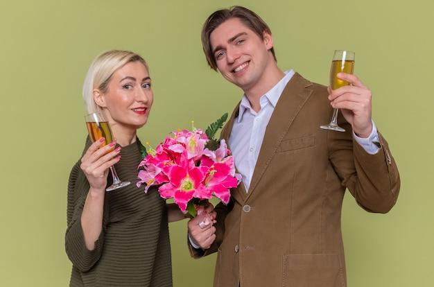 Giovane bella coppia uomo felice con bouquet di fiori e donna che tiene bicchieri di champagne