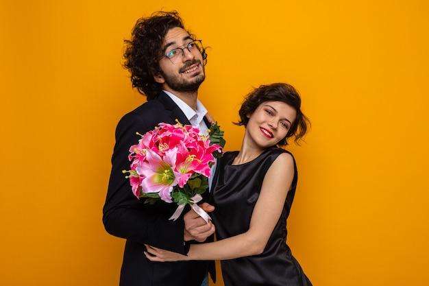 Giovane bella coppia uomo felice con bouquet di fiori e donna che sorride allegramente abbracciando felicemente innamorato che celebra san valentino