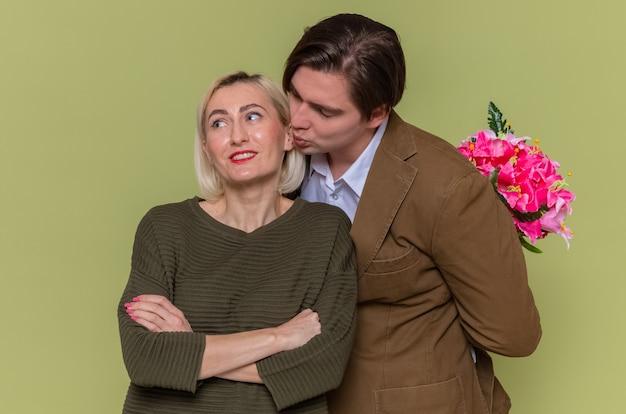 녹색 벽 위에 서있는 국제 여성의 날을 축하하는 그의 사랑스러운 여자 친구에게 키스하려고 그의 뒤에 꽃의 꽃다발과 함께 젊은 아름다운 부부 행복한 사람