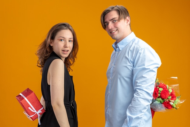 Young beautiful couple happy man with bouquet of red roses behind his back and woman with present behin looking at camera smiling cheerfully celebrating valentines day standing over orange background