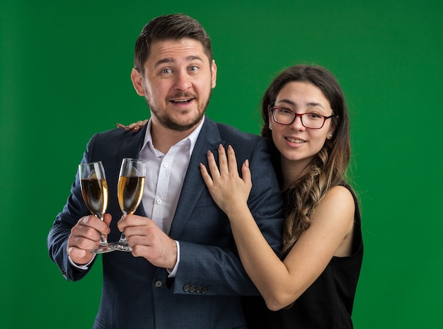 Giovane bella coppia uomo felice con bicchieri di champagne e donna sorridente che abbraccia felice innamorato insieme festeggiando san valentino in piedi sul muro verde