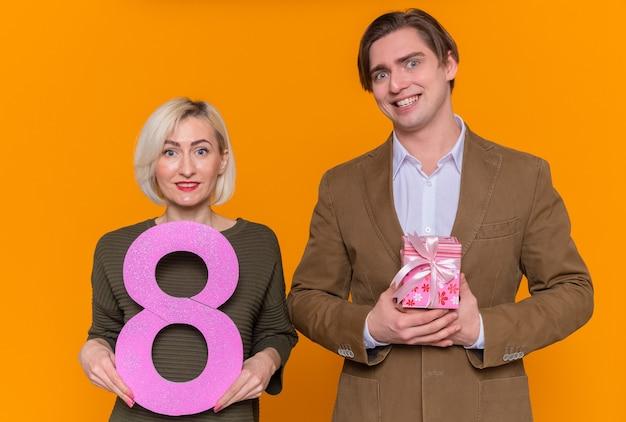 プレゼントと8番を保持している女性と若い美しいカップル幸せな男