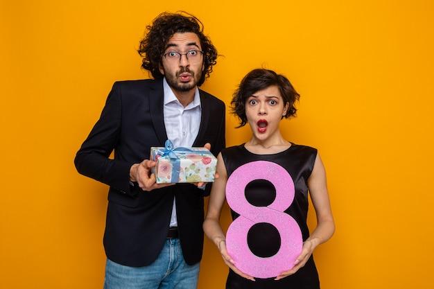 Giovane bella coppia uomo felice con regalo e donna con numero otto guardando la telecamera stupita e sorpresa celebrando la giornata internazionale della donna 8 marzo in piedi su sfondo arancione