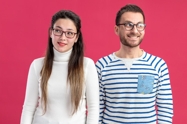 Giovane bella coppia felice uomo e donna in abiti casual guardando a parte con il sorriso su facce felici per celebrare il giorno di san valentino concetto in piedi sul muro rosa