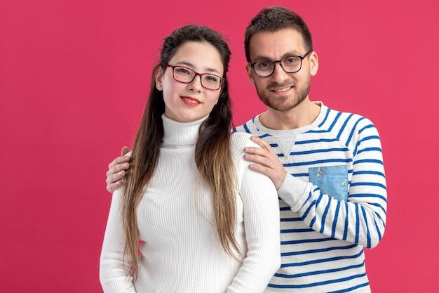 Giovane bella coppia felice uomo e donna in abiti casual con gli occhiali felici innamorati insieme abbracciando celebrando il concetto di san valentino in piedi sul muro rosa