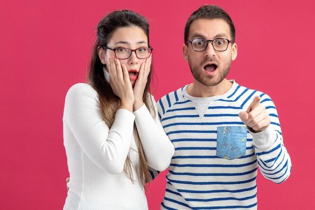 Giovane bella coppia felice uomo e donna in abiti casual con gli occhiali guardando la telecamera stupito e sorpreso che celebra il concetto di san valentino in piedi sul muro rosa