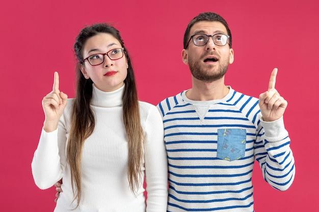 Giovane bella coppia felice uomo e donna in abiti casual con gli occhiali guardando in alto sorpreso indicando con il dito indice in su per celebrare il concetto di san valentino in piedi su sfondo rosa