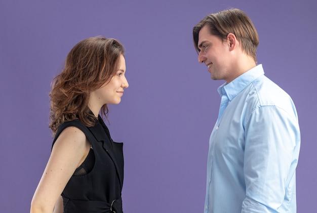 Giovane bella coppia felice uomo e donna guardando l'altro sorridente per celebrare san valentino in piedi su sfondo blu