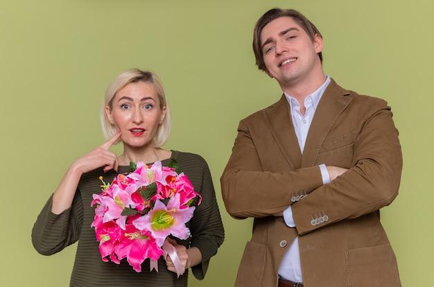 Giovane bella coppia felice uomo e donna con bouquet di fiori guardando davanti sorridendo allegramente celebrando la giornata internazionale della donna in piedi sopra la parete verde