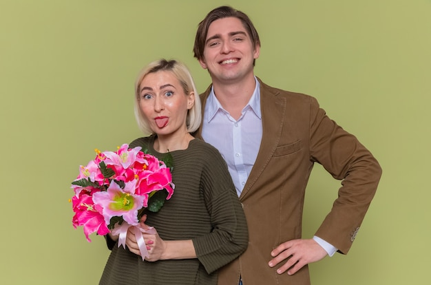 Giovane bella coppia felice uomo e donna con bouquet di fiori guardando davanti sorridente divertendosi spuntavano lingua celebra la giornata internazionale della donna in piedi sopra la parete verde