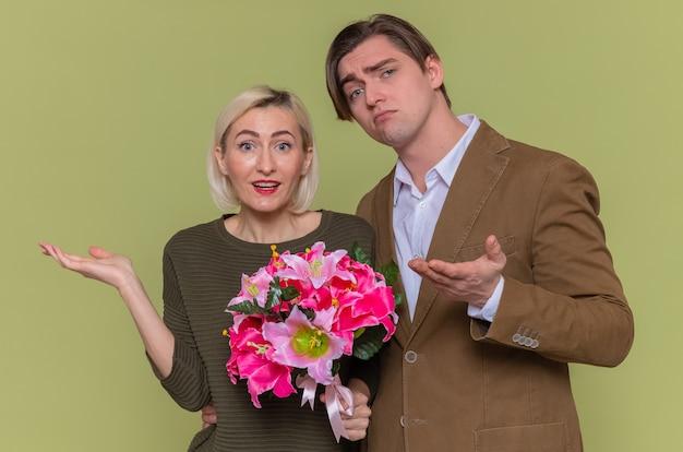 Giovane bella coppia felice uomo e donna con il mazzo di fiori guardando la parte anteriore con le braccia alzate sorridente avendo dubbi che celebra la giornata internazionale della donna in piedi sopra la parete verde