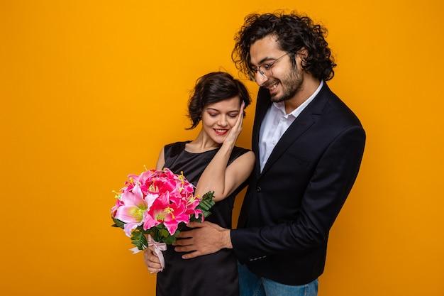 Giovane bella coppia felice uomo e donna con bouquet di fiori sorridendo allegramente abbracciando felice in amore che celebra la giornata internazionale della donna 8 marzo in piedi su sfondo arancione