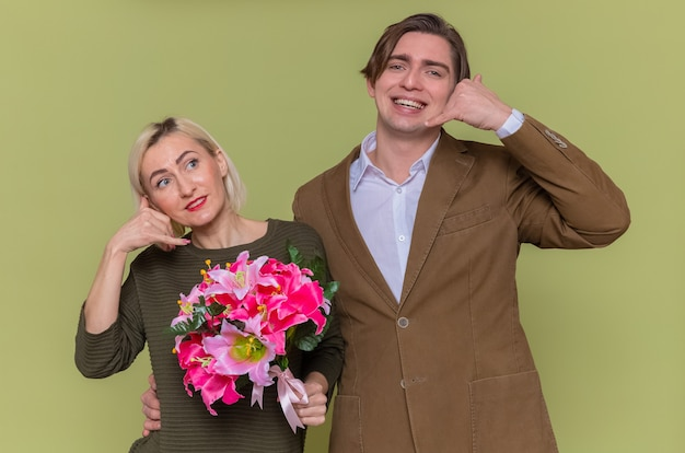 Young beautiful couple happy man and woman with bouquet of flowers