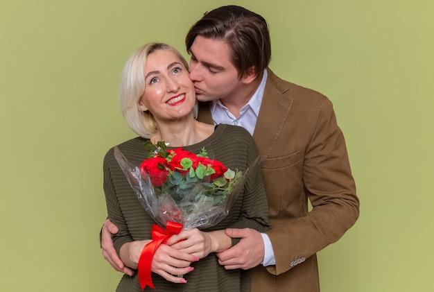 Giovane bella coppia felice uomo e donna con bouquet di rose rosse che abbraccia felice nell'amore insieme per celebrare la giornata internazionale della donna in piedi sopra la parete verde