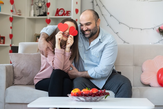 Young beautiful couple happy man and woman with hearts made from cardboard smiling having fun together celebrating saint valentine's day sitting on a couch in light living room