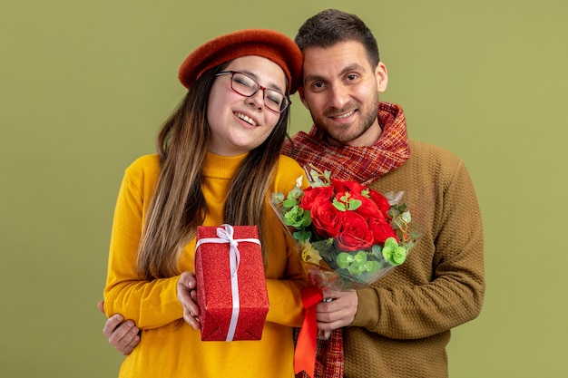 Giovane bella coppia donna felice in berretto con presente e uomo con bouquet di rose rosse guardando la telecamera sorridendo felice innamorato insieme celebrando il giorno di san valentino in piedi sul muro verde