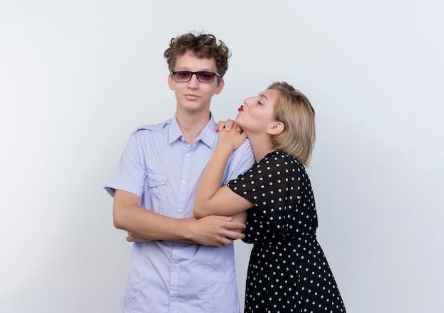 Молодая красивая пара счастливая женщина обнимает своего уверенного парня, целуя его над белой стеной