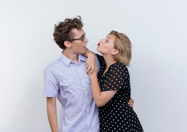 Молодая красивая пара счастливая женщина обнимает своего удивленного парня и целует его над белой стеной