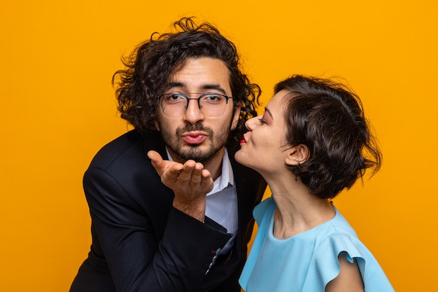 Young beautiful couple happy woman kissing her smiling blowing a kiss boyfriend celebrating international women's day march 8 standing over orange background