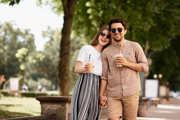 Young beautiful couple have a fun and walking on city streets and drinking coffee