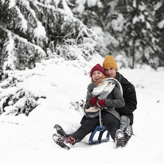 Young beautiful couple having fun sitting on the sleigh
