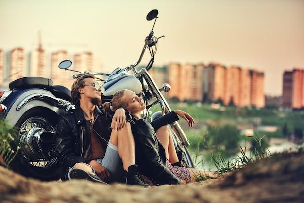 청바지와 티셔츠에 포즈 거리 야외 초상화에 복고풍 오토바이에 대한 세련된 의류에 젊은 아름 다운 부부 멋쟁이, 수염 난 남자 금발 소녀가 함께 여행