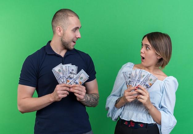 Giovane bella coppia in possesso di contanti che si guardano sorpresi e stupiti in piedi sul muro verde