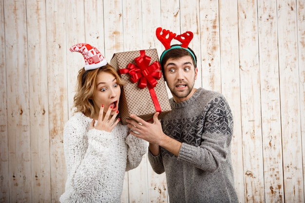 Young beautiful couple holding christmas gift over wooden wall