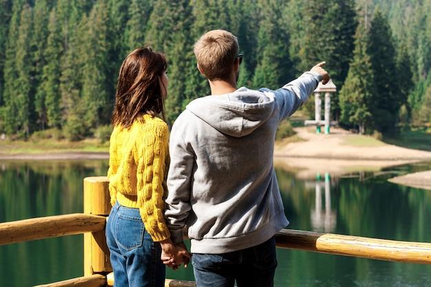 Young beautiful couple holding hands, enjoying mountains lanscape near lake