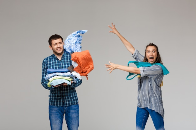 Young beautiful couple holding wash clothes, fighting over grey wall