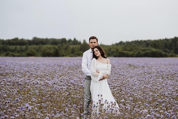 咲く紫色のフィールドで抱き締める若い美しいカップル