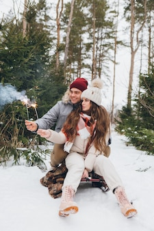젊은 아름다운 부부는 썰매에 앉아 있는 동안 겨울 침엽수림에서 폭죽을 껴안고 태웁니다. 배경에 크리스마스 트리가 있는 공원. 크리스마스 분위기. 틴팅.