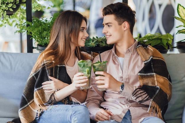 Молодая красивая пара в кафе. мальчик и девочка пьют коктейль на летней террасе.
