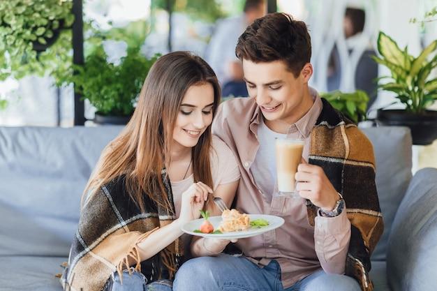 카페에서 젊은 아름 다운 커플. 소년과 여성은 여름 테라스에서 칵테일을 마신다
