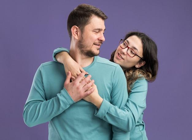 파란색 캐주얼 옷 행복하고 쾌활한 남자와 보라색 벽 위에 서있는 발렌타인 데이를 축하하는 사랑에 행복을 포용하는 젊은 아름 다운 부부