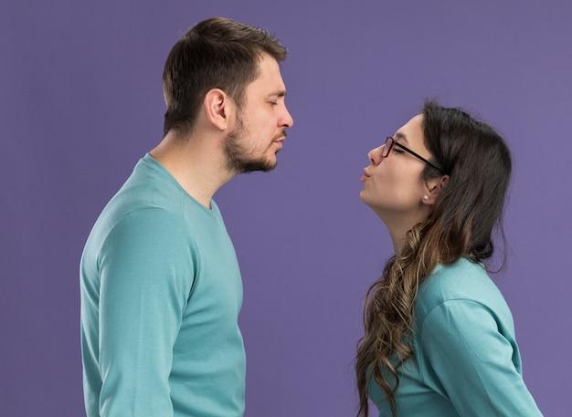파란색 캐주얼 옷 행복하고 쾌활한 남자와 여자가 보라색 벽 위에 서있는 사랑에 행복 키스하려고 젊은 아름 다운 부부