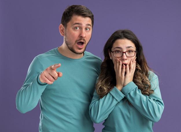 파란색 캐주얼 옷 남자와 여자의 젊은 아름 다운 부부는 깜짝 놀라게하고 보라색 벽 위에 서 놀란