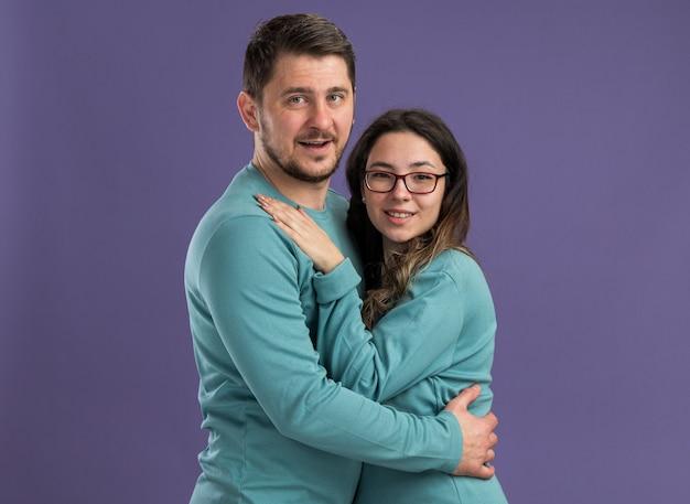 青いカジュアルな服を着た若い美しいカップル男女が陽気な笑顔を抱きしめ、紫色の壁の上に立って一緒に恋に幸せ