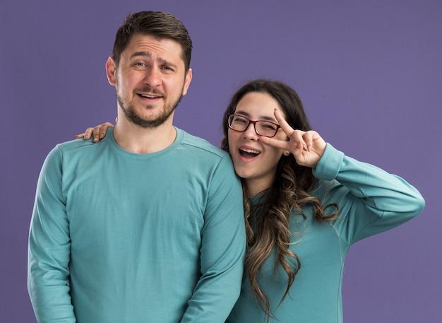 파란색 캐주얼 옷 남자와 여자 행복하고 쾌활한 젊은 아름 다운 부부는 보라색 벽 위에 서있는 사랑에 v 기호 행복을 보여주는 재미 미소