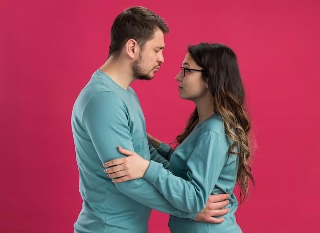 파란색 캐주얼 옷 남자와 여자의 젊은 아름 다운 부부는 서로 사랑에 행복 한 그의 여자 친구가 분홍색 벽 위에 서서 키스하려고 서로를 찾고