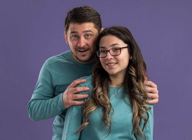 파란색 캐주얼 옷 남자와여자가 함께 보라색 벽 위에 서 사랑에 유쾌 하 게 행복 하 게 웃는 젊은 아름 다운 부부