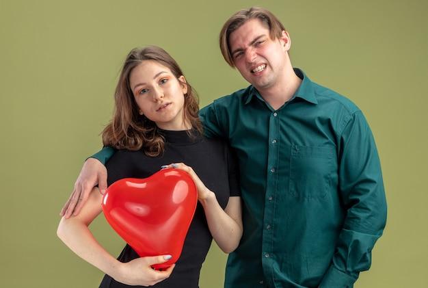 캐주얼 옷에 젊은 아름 다운 부부 혼란 남자와 녹색 벽 위에 서 발렌타인 데이를 축하 심장 모양의 풍선과 함께 긍정적 인 여자