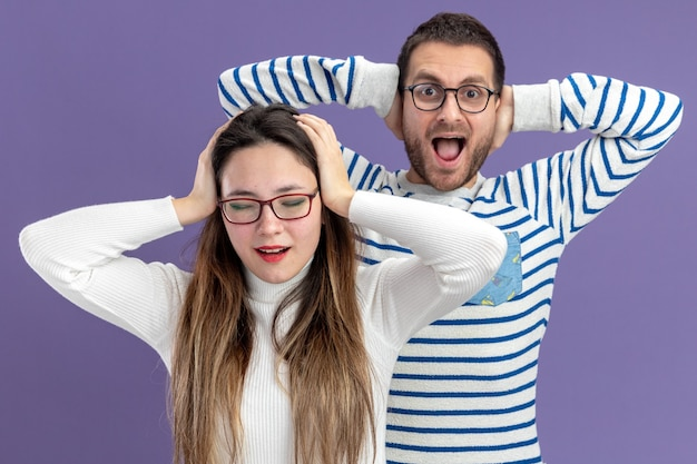 캐주얼 옷에 젊은 아름 다운 부부 행복 하 고 놀란 남자와여자가 보라색 벽 위에 서 머리 발렌타인 데이 개념에 손을 잡고