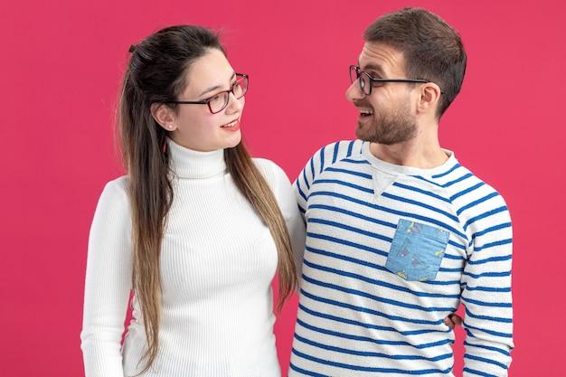 ピンクの壁の上に立ってバレンタインデーを祝って元気に笑顔でお互いを見て眼鏡をかけている幸せな男性と女性のカジュアルな服を着た若い美しいカップル